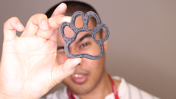 A man looking through a paw made with the help of a 3D printer from Tech Lending.