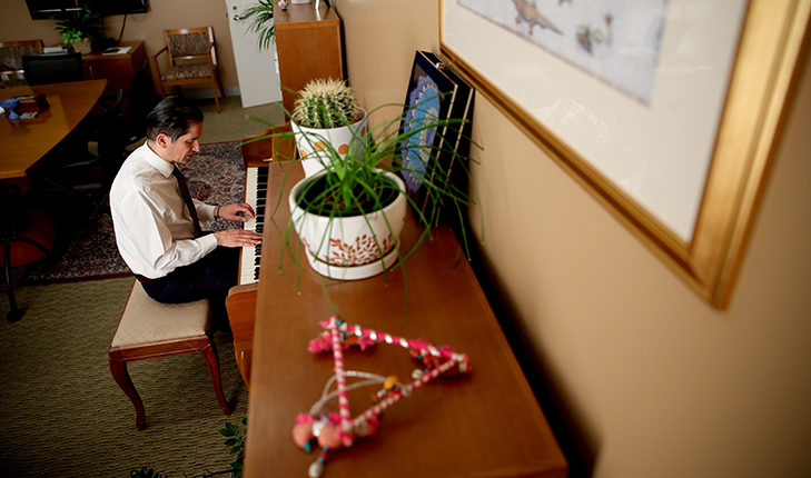 (New Provost Saúl Jiménez-Sandoval started playing the piano four years ago. He plays in this office to collect this thoughts. Photo by University photographer Cary Edmondson.)
