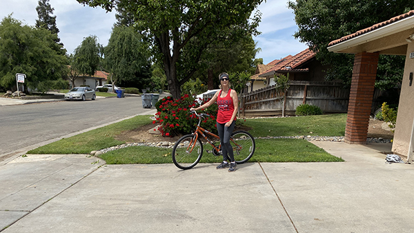 Woman standing with bicycle on driveway