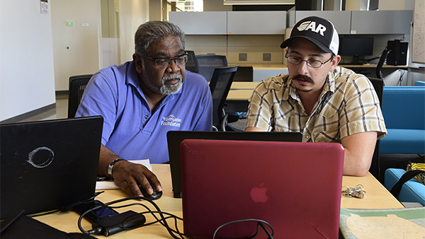 Dr. Dave Goorahoo, professor in the Department of Plant Science, sits with a student.