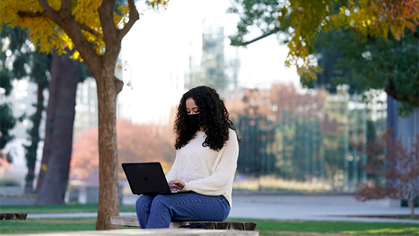 A student works on a laptop in the Peace Garden at Fresno State.