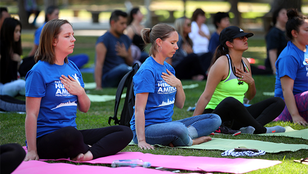 Staff and students participate in healthy campus week with a yoga activity.