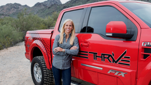 Danielle Bryant, owner of THRIVE Construction, stands next to a red THIVE truck.