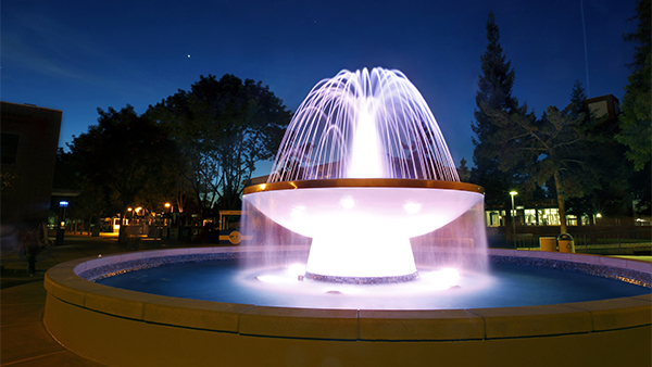 Fresno State fountain glowing at night.