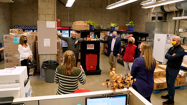 Masked men and women standing in the Student Cupboard on campus during presentation of $1.5 million gift by the Amendola  family.