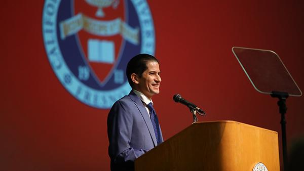 Interim President Saul Jimenez-Sandoval at a podium with the University seal behind him.