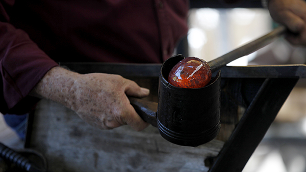 Person holding hot glass to mold