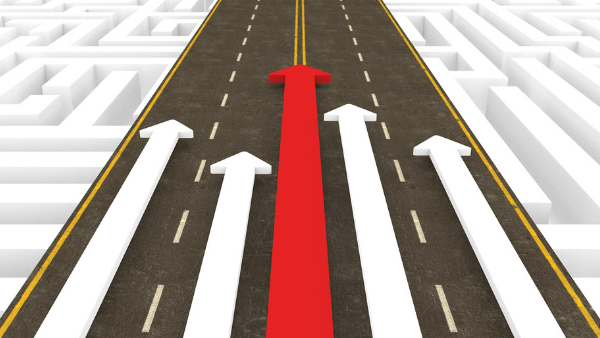 Cartoon of traffic lanes with four white arrows pointed ahead and the arrow in the middle is red.