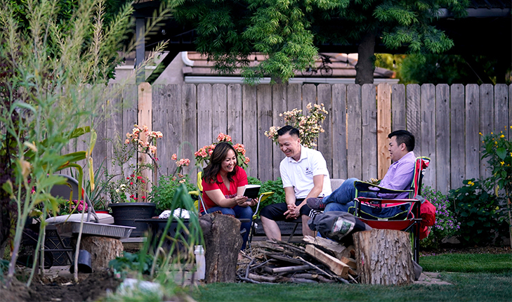 Phong Yang, director of Admissions and Recruitment, sitting with wife and son in the back yard.