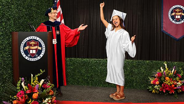 Interim President Saul Jimenez-Sandoval at a podium with the University seal standing next to a graduating senior.