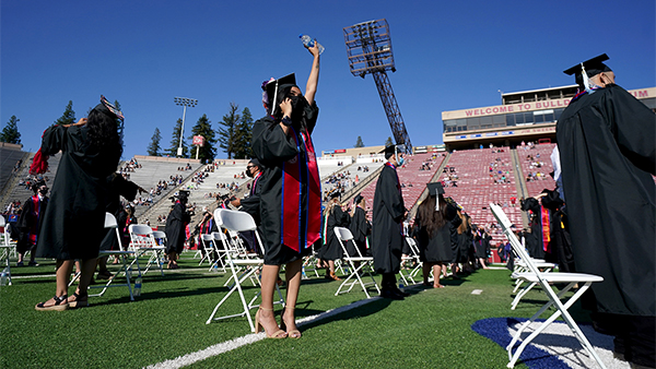 A student stands with her arm raised during commencement ceremonies at Bulldog Stadium.