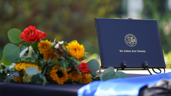 Flowers and blue commencement degree holder on a table.