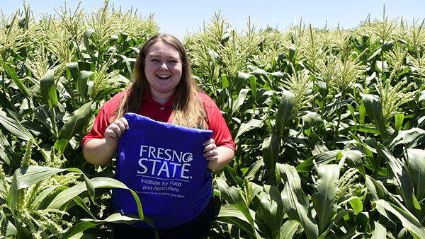 Student holds a blue Fresno State bag in a corn field.
