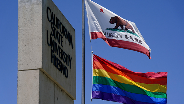 The rainbow pride flag flies under the California state flag at Fresno State.