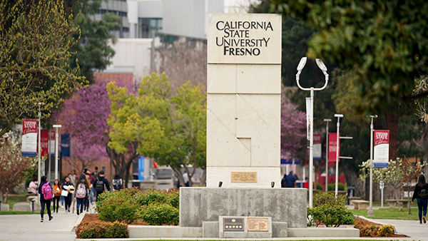 California State University, Fresno sign in front of rose garden. Students walking around and trees are in full bloom.
