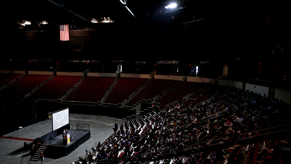 Inside Save Mart Center with employees listening to a speaker on stage.