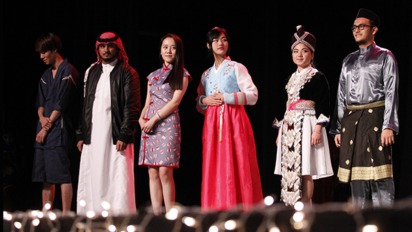 Students on stage in attire from their culture.