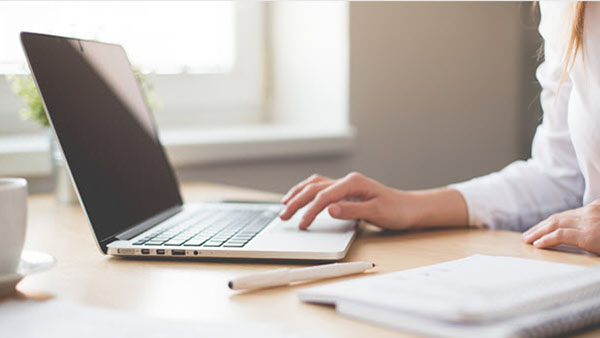 Woman's hand on a laptop working