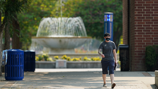 Male student walking, fountain in background
