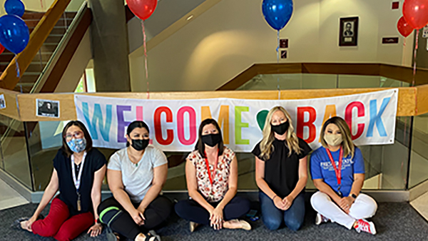 Women sitting in front of a welcome back sign. Balloons of red and blue around them.