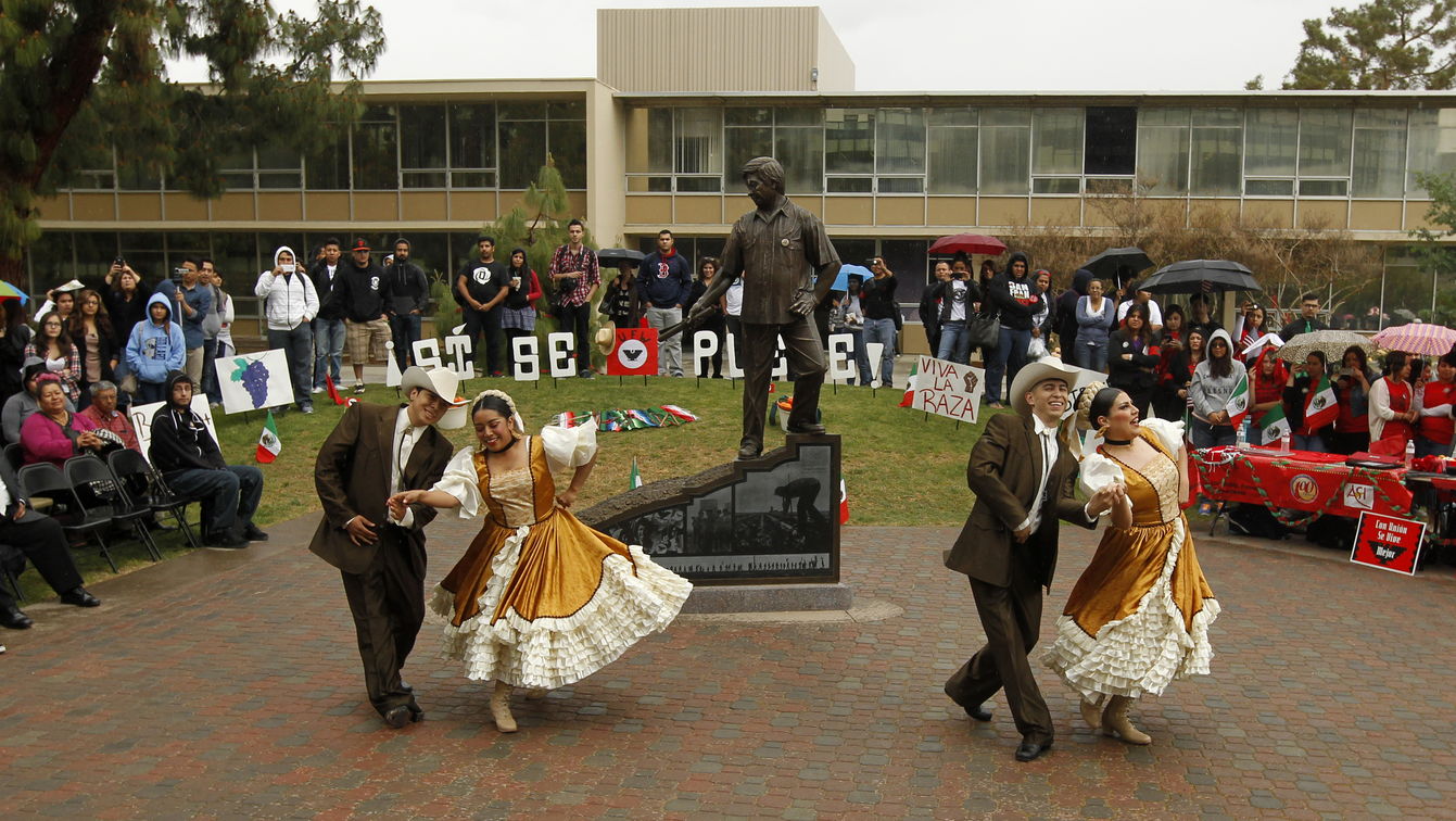 Hispanic dancers in front a crowd at the Cesar Chavez statue in the Peace Garden.